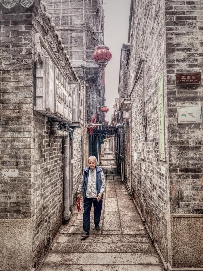 Free An Old Woman Walking In The Alley Stock Image - 106962121