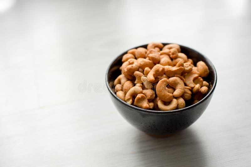 Anacardi salati in ciotola ceramica nera su gray immagine stock