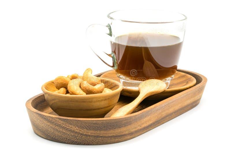 Anacardi salati e una tazza di caffè nero in un vassoio fotografie stock