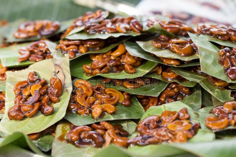 Anacardos tailandeses del estilo con el azúcar marrón dulce en las hojas imagen de archivo
