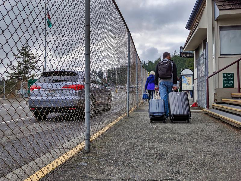 Passenger leaving the island ferry and hauling luggage toward the long term parking. Anacortes, WA / USA - circa November, 2019: Passenger leaving the island royalty free stock images