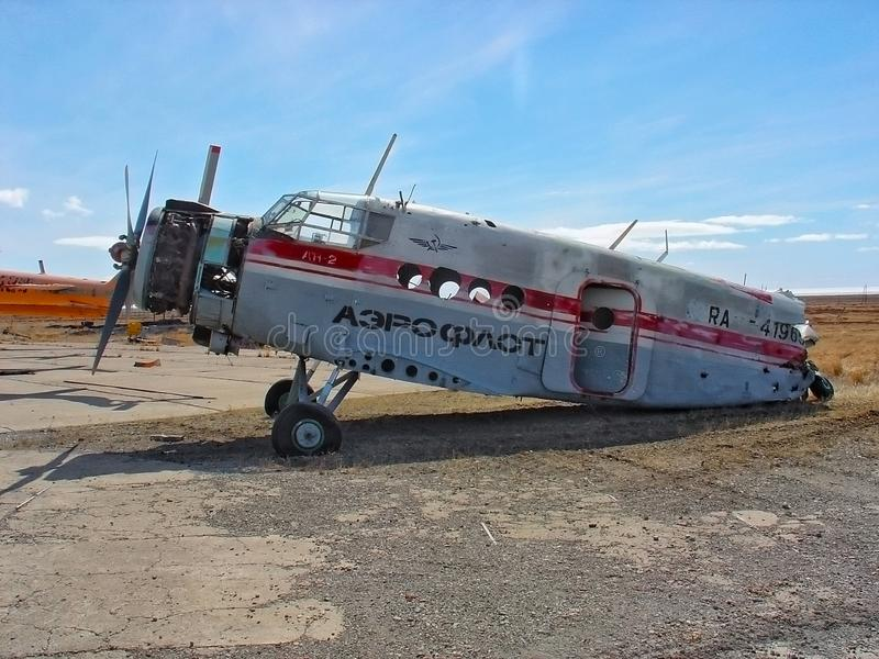 Debris of vintage Soviet civil passenger airplane with no tail and wings corroding outdoors at scrap metal storehouse on scenic na royalty free stock image
