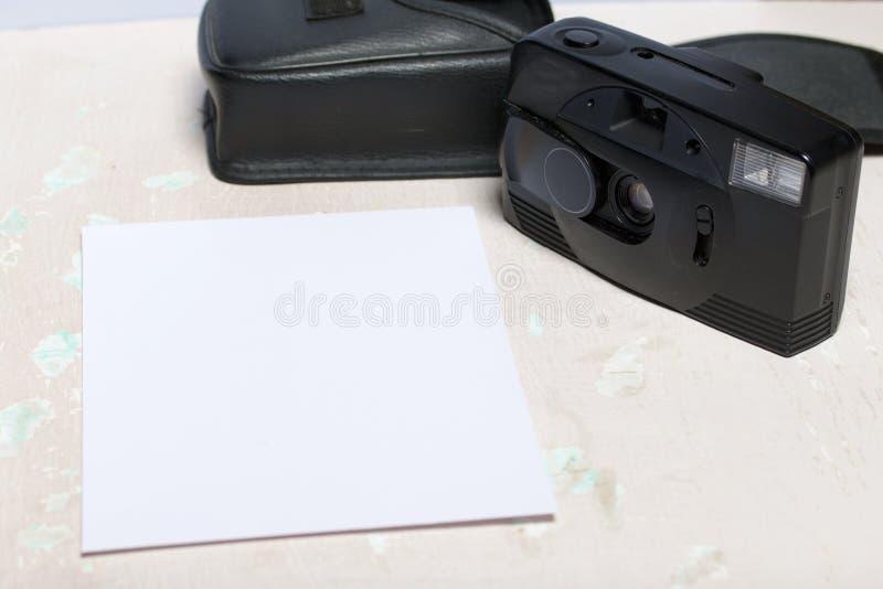 Analógico velho 35mm da câmera do filme Mentiras na superfície da tabela Perto da tampa para ele Perto de uma folha branca do pap foto de stock