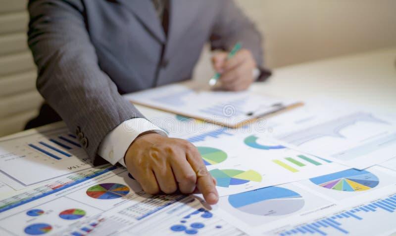 analisando cartas e gráficos da renda com calculadora imagens de stock
