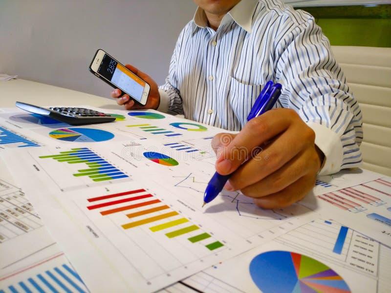 analisando cartas e gráficos da renda com calculadora Fim acima Análise financeira do negócio e conceito da estratégia imagens de stock