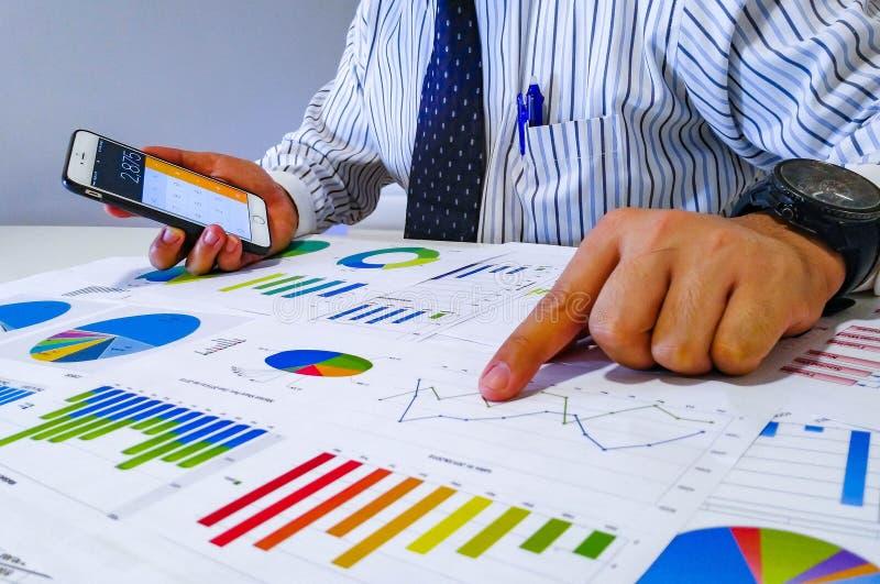 analisando cartas e gráficos da renda com calculadora Fim acima Análise financeira do negócio e conceito da estratégia imagem de stock royalty free