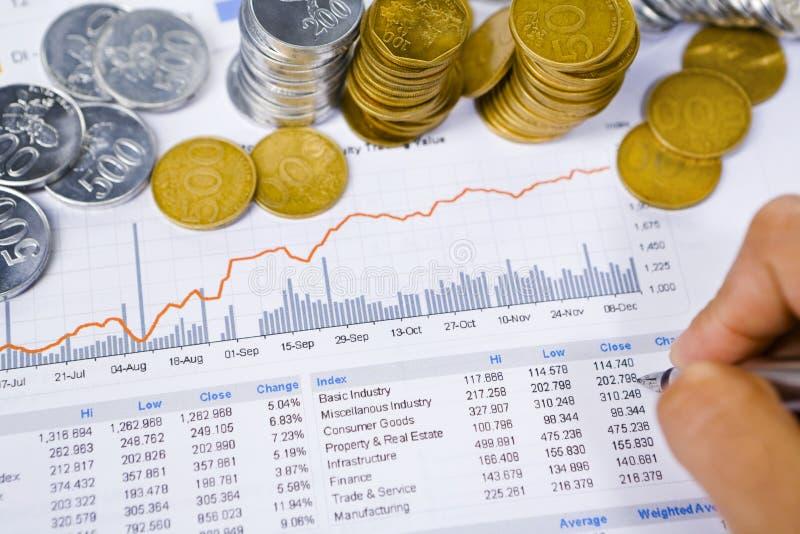 Analisando o relatório financeiro com as moedas em torno dele imagem de stock