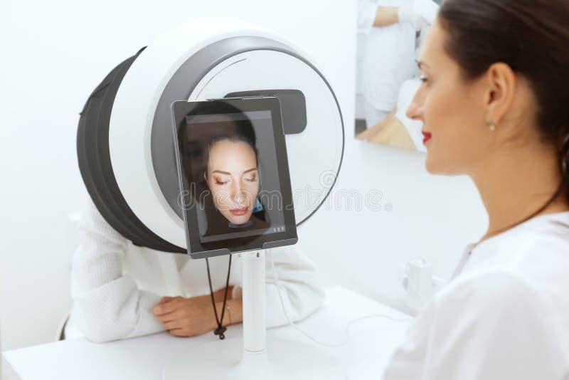 Analisi della pelle del fronte Donna a cosmetologia che fa sistema diagnostico della pelle immagine stock