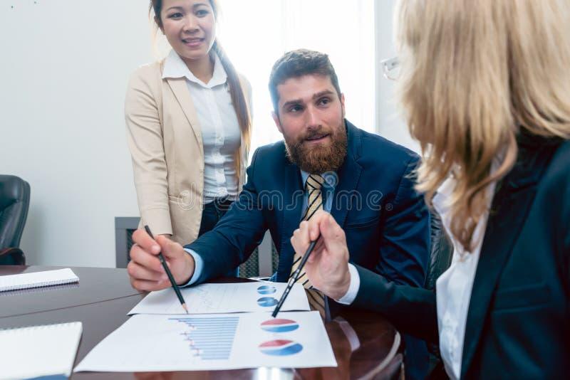 Analista do negócio que sorri ao interpretar os relatórios financeiros sh fotografia de stock