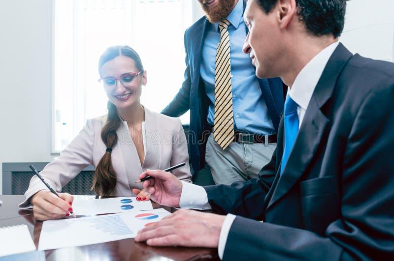 Analista do negócio que sorri ao interpretar relatórios financeiros fotografia de stock royalty free