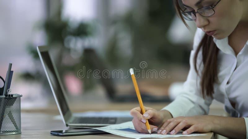 Analista financeiro profissional que faz anotações em papéis, mulher que trabalha no relatório imagens de stock