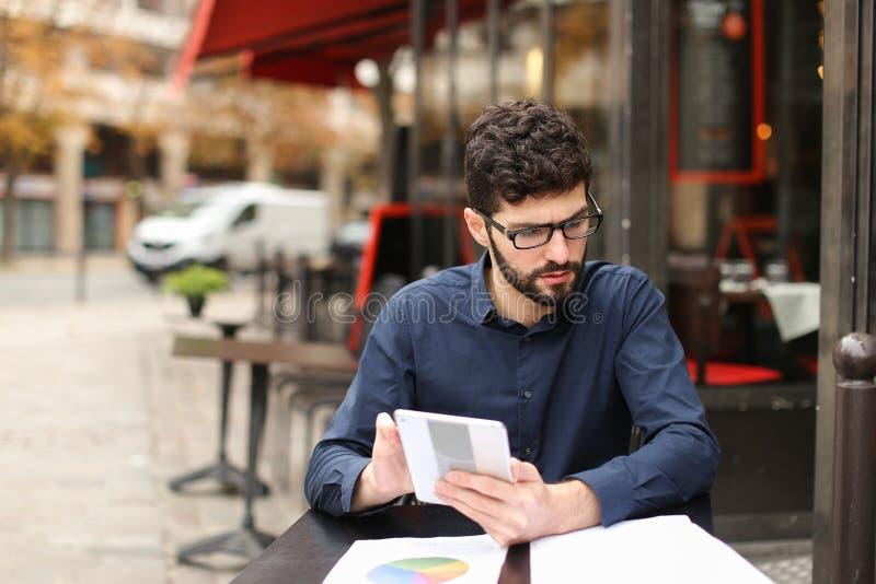 Analista financeiro que senta-se com a tabuleta na tabela e no descanso do café fotos de stock