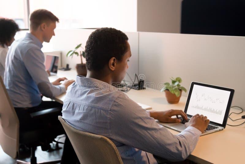 Analista negro focado trabalhando em laptop no espaço de trabalho em conjunto fotografia de stock