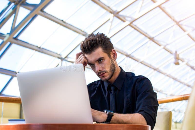 Analista pensativo de la propiedad inmobiliaria comercial del hombre que trabaja en el ordenador portátil en compañía acertada fotos de archivo libres de regalías