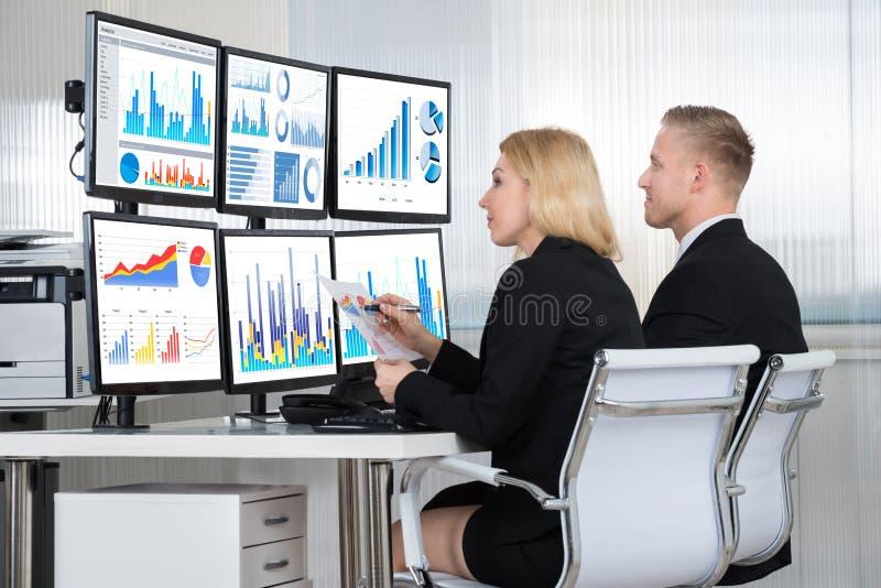 Analistas financeiros que usam computadores no escritório imagens de stock royalty free