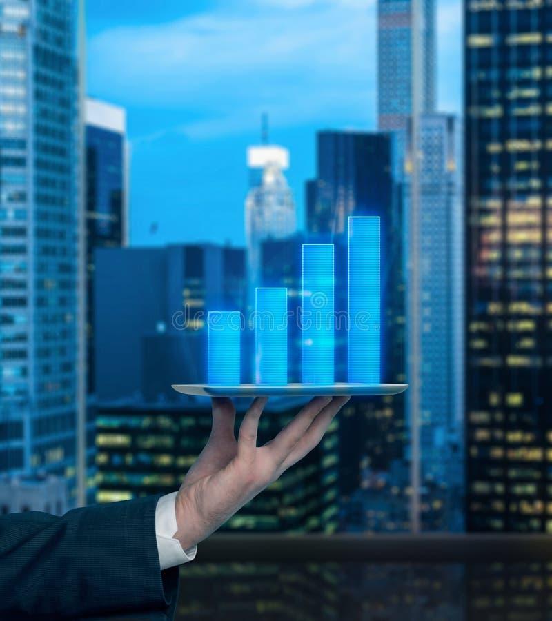 Analityk ręka trzyma gadżet z prętowej mapy projekcją oczekiwać dochód firma obrazy stock