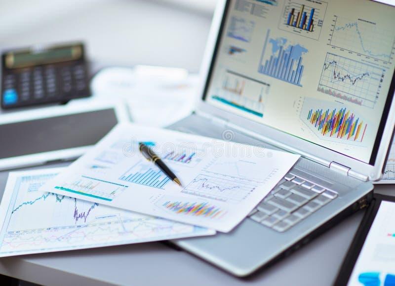 Analizar cartas de la inversión con el ordenador portátil imagen de archivo