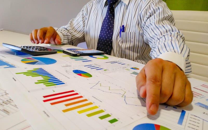 analizar cartas y gráficos de la renta con la calculadora Cierre para arriba Análisis financiero del negocio y concepto de la est foto de archivo