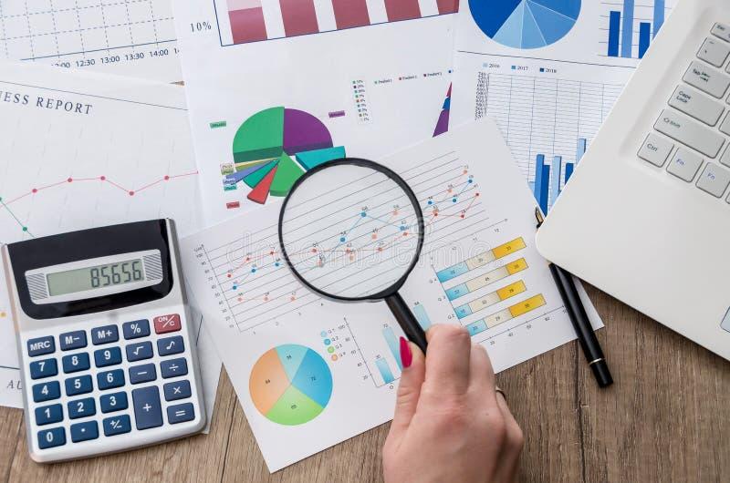 Analizujący biznesowych wykresy z powiększać - szkło fotografia royalty free