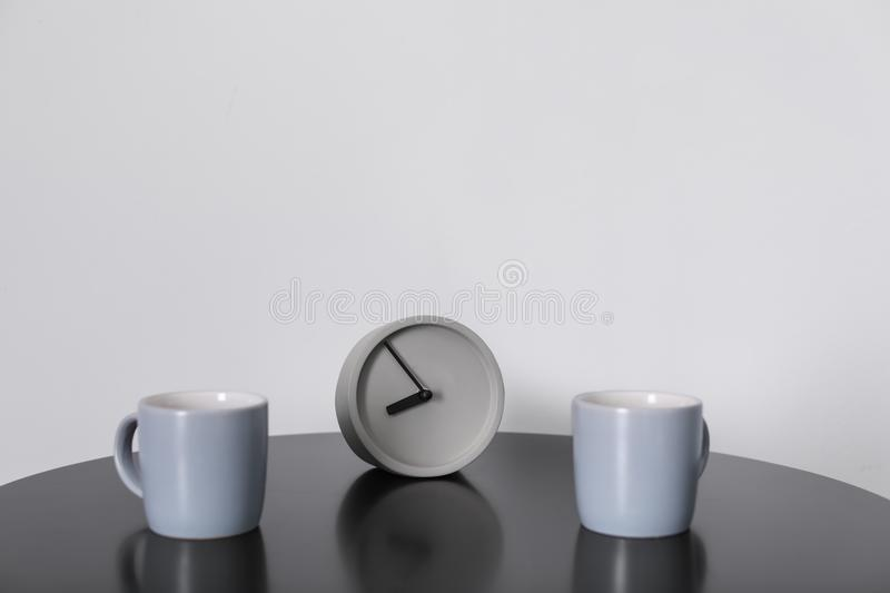 Analog alarm clock and cups on table stock images