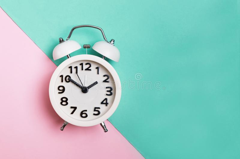 Analog alarm clock on pink and mint pastel colors background, stock photo