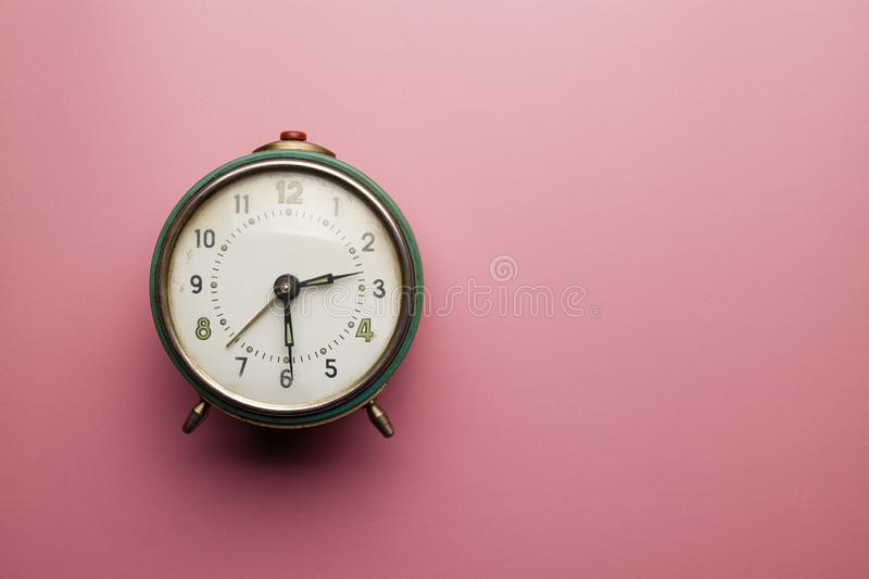 Analog alarm clock on pink table background royalty free stock images