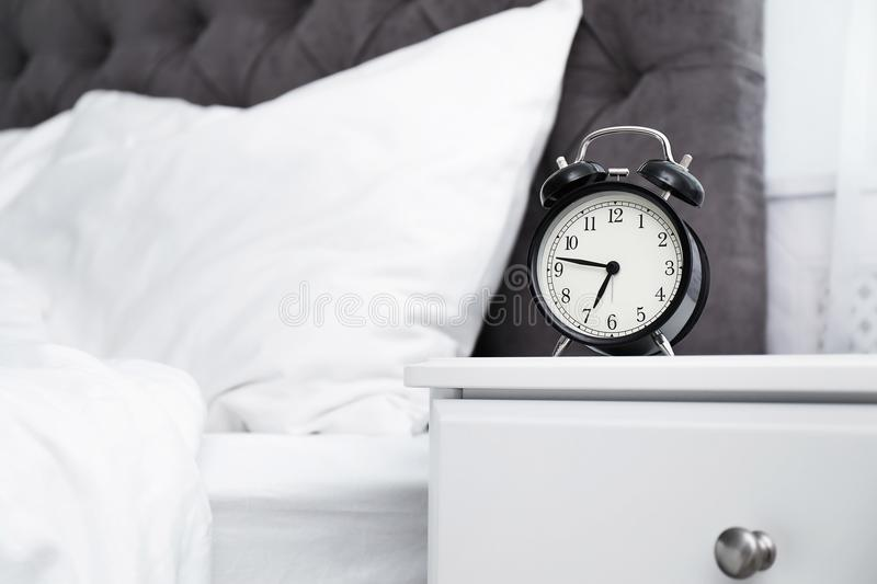 Analog alarm clock on table in bedroom. Time of day royalty free stock photos
