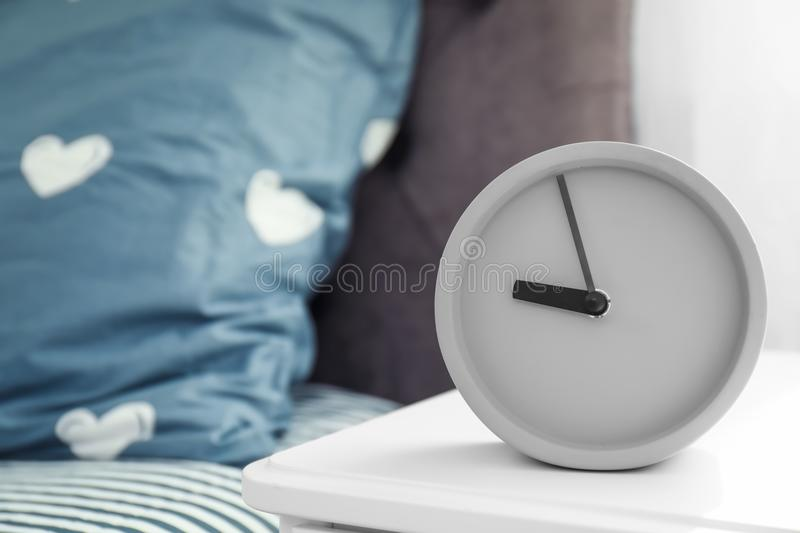 Analog alarm clock on table in bedroom. Time of day stock images