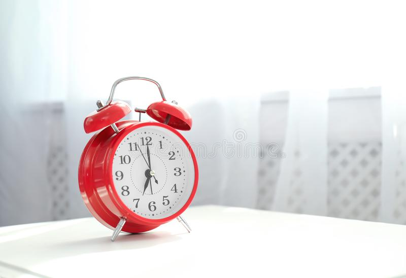 Analog alarm clock on table indoors. Time of day stock image