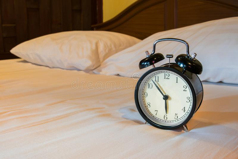 Analog alarm clock is on white bed. Time in the morning royalty free stock photos
