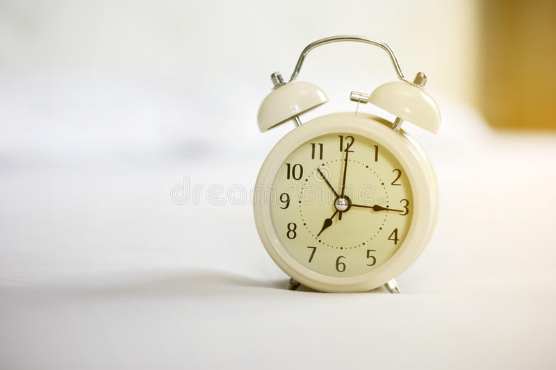 Analog alarm clock on white bed, time in the mornign with a brig stock photos