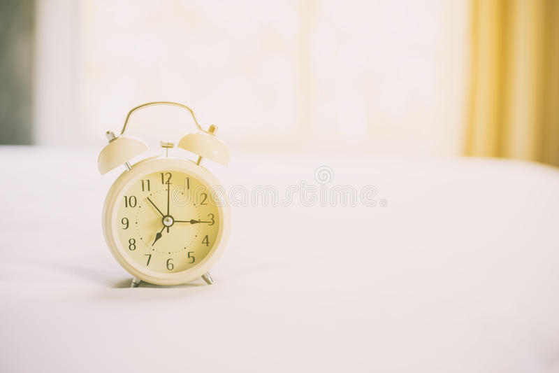 Analog alarm clock on white bed, time in the morning with a brig stock image