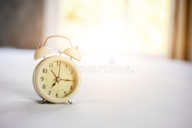 Analog alarm clock on white bed, time in the morning with a bright sunshine royalty free stock photos