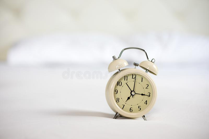 Analog alarm clock on white bed, time in the morning with a brig royalty free stock photos