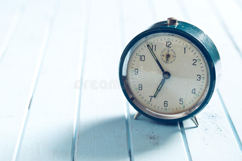 Analog alarm clock on wooden table. The analog alarm clock on wooden table stock photo