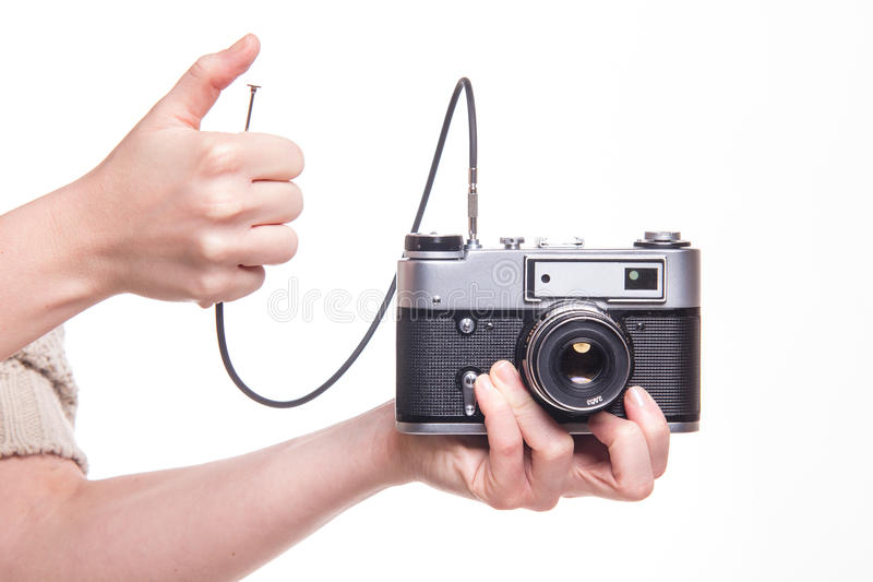 Analog camera with cable release and hand. Classic 35mm old analog camera on white - studio shoot royalty free stock photography