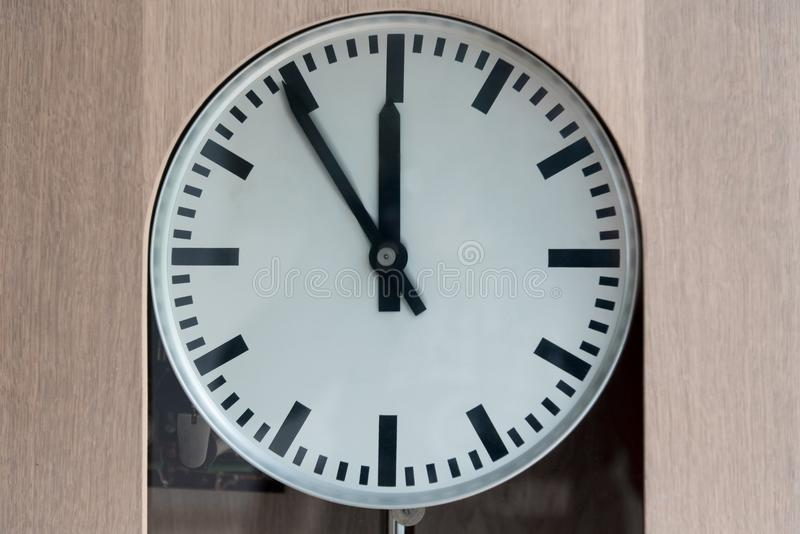 Analog clock showing five to twelve isolated on black. Old analog clock showing five to twelve stock photography