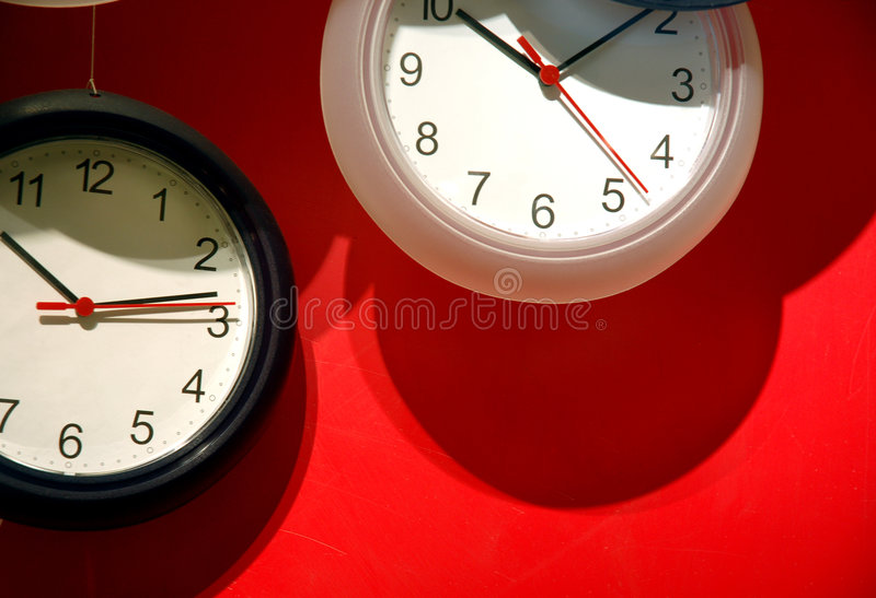 Analog clocks on red wall. Two 12-hour analog clocks on a red wall stock photos
