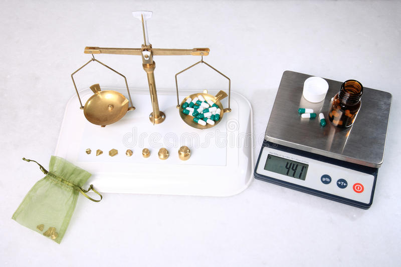 Analog and digital scale. Analog and digital pharmacy scales with pills royalty free stock photo