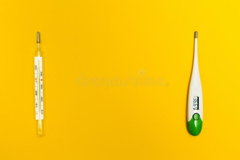 Analog and digital thermometer on a yellow background, with space for text. The temperature of 36.6 C stock photo