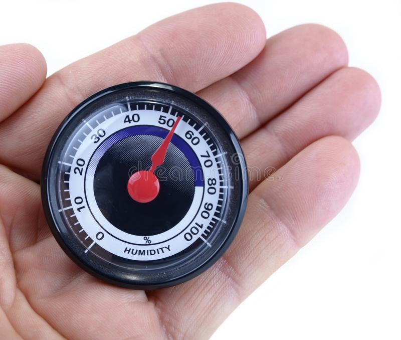 Analog humidity meter in the hand on white. Analog humidity meter in the hand on white royalty free stock images
