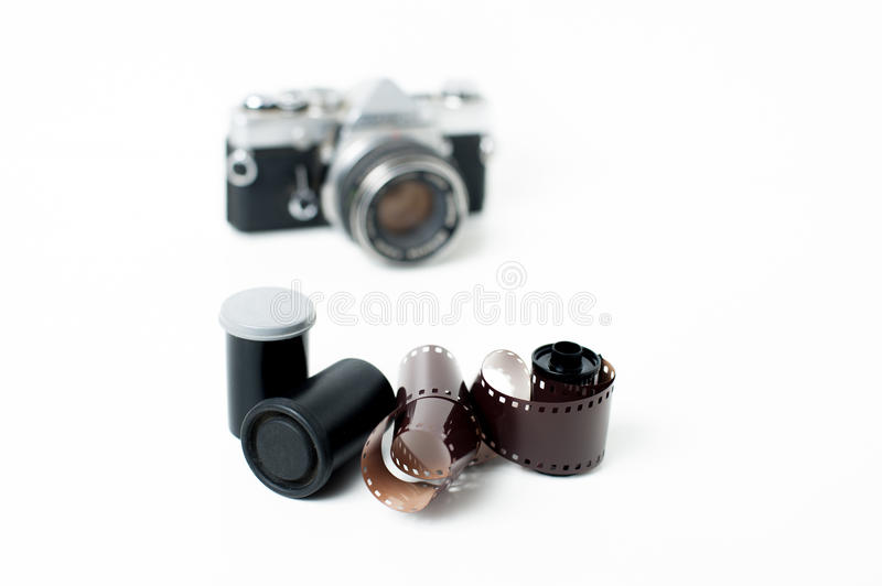 Analog photo reels with camera in background. Analog photo reels with vintage camera out of focus in background on white stock photography