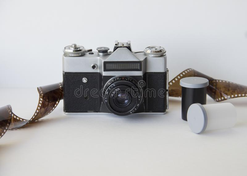 Old camera and film on white background. Analog photography: a camera with a lens and film inside on a white background stock photo