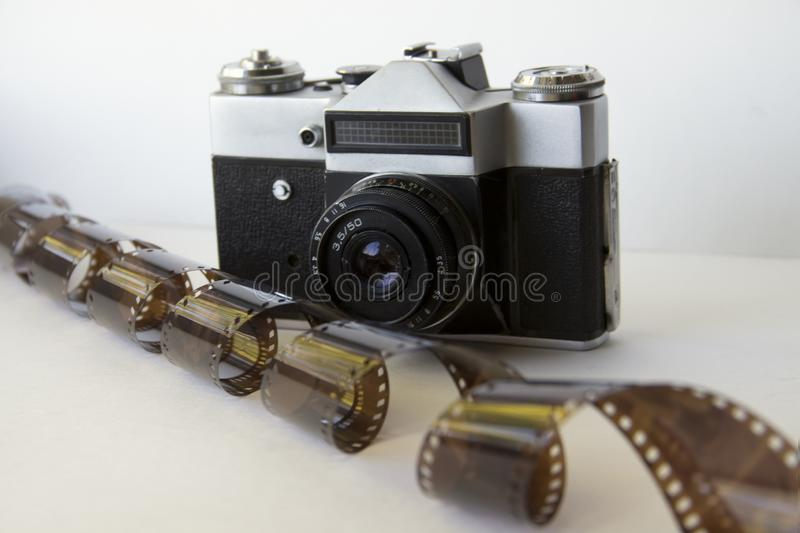 Old camera on white background with film. Analog photography: a camera with a lens and film inside on a white background stock images