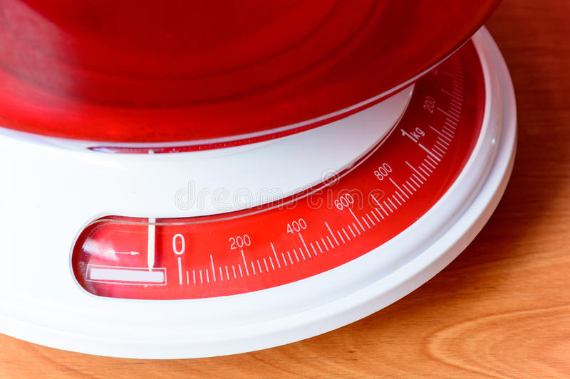 Analog red kitchen scales on the wooden table. Preparation for baking. Kitchen tools stock image