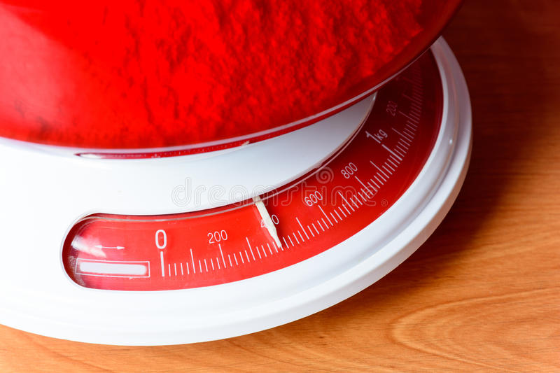 Analog red kitchen scales on the wooden table. Preparation for baking. Kitchen tools royalty free stock photography