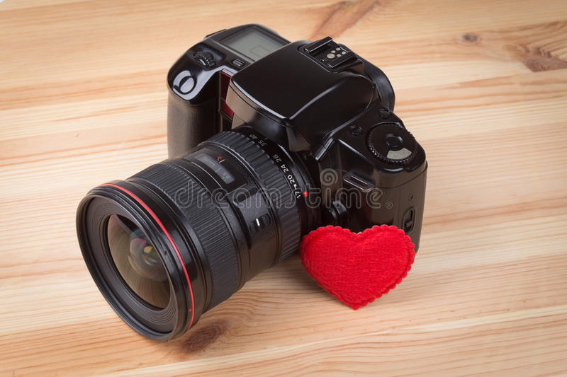 Analog SLR camera. With heart on wooden background royalty free stock photography