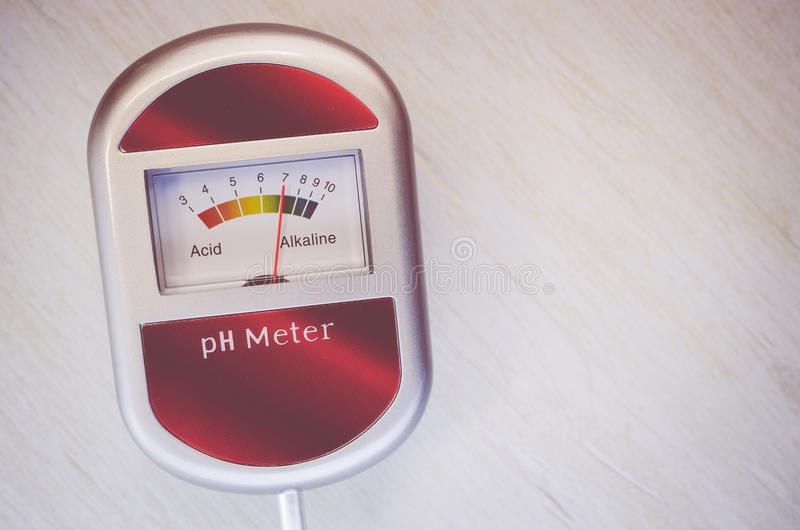 Analog soil ph meter on a wood surface. Analog tool to measure soil ph on a light tint wood background royalty free stock photos