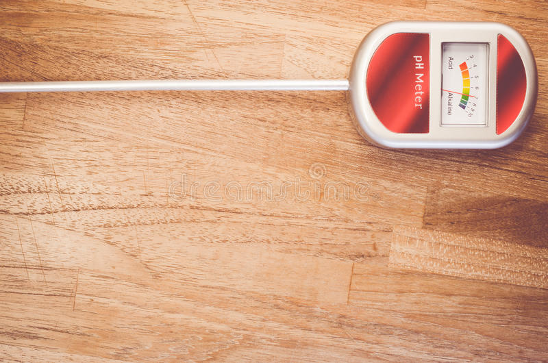 Analog soil ph meter on a wood surface. Analog tool to measure soil ph on a natural tint wood background royalty free stock photos