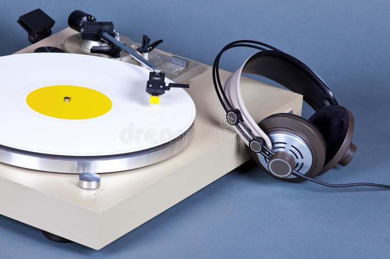 Analog Stereo Turntable Vinyl Record Player with White Disk. And Headphones royalty free stock images